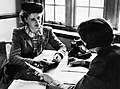 Iris Joyce talks with a recruiting officer as she enrols in the Women's Land Army during 1942. D8793.jpg