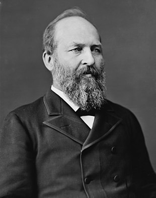 Garfield wears a double breasted suit and has a full beard and receding hairline
