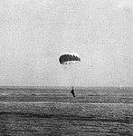 Japanese pilot with parachute descends towards the water, 17 April 1945.jpg