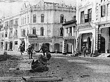 Japanese troops running along a rubble road in front of old colonial buildings.