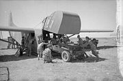 Four men pushing a jeep into a glider via teh raised front cockpit