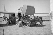Waco glider with the front cockpit raised and four men pushing a jeep inside