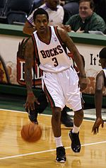 "A man, wearing a green jersey with a word ""BUCKS"" and the number ""3"" written in the front, is dribbling a basketball."