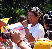 A man with a hat and a white t-shirt singing to a microphone.