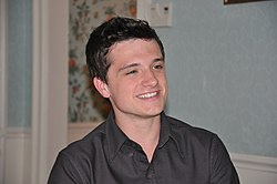 Hutcherson with slicked-back hair, wearing a black button-up dress shirt