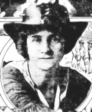 A black and white photograph of a woman in a boater-style hat