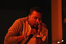 An image of a man singing into a microphone against red light.