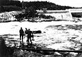 Kastenotfiske fra land i Skoltefossen. Noten skal til å kastes. I bakgrunnen en bro. Neiden 1948 - Norsk folkemuseum - NF.11103-001.jpg