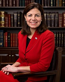A grinning woman sitting in a chair while wearing a red suit