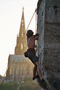 Un grimpeur sur un bâtiment vue en contre-jour