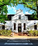 La Gratitude was built by the Rev. Meent Borcherds, the parson at Stellenbosch from 1786 to 1830, in 1798. He was born at Jangum, East Friesland, in 1762. The house is a U-shaped building with one of the earliest neo-classical pilaster-gables. The pilasters are repeated between the windows. This gives an exceptional dignity to the facade and creates an air of aristocratic pride.