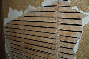 Lath and plaster - Partially-exposed wallpapered lath and plaster illustrating the technique.  Example from the Winchester Mystery House, constructed between 1884 and 1922