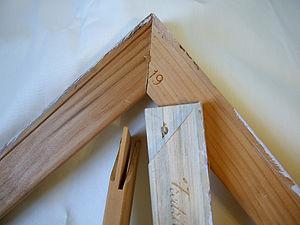 Stretcher bar - A fully assembed stretcher bar corner. Two unassembed stretcher bars displaying corner mitre construction.