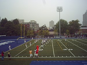 Official (Canadian football) - The referee can be seen with the white cap behind the offensive team (in blue) in this CIS football game.