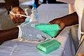 Mains africaines portant les gants qui offre un plat de nourriture.jpg