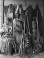 Maori carved figure wearing a piupiu and tiki, standing against a wall with weapons, implements and cloaks. ATLIB 273585.png