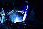 Matthew Crozier, an 11th Civil Engineer Squadron structural apprentice, assists Fabian Moore, welder, as he welds a metal bar in place at Joint Base Andrews on Feb. 13, 2019 (190213-F-PG738-9278).jpg