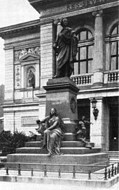 black-and-white photograph of a statue of a robed male figure on a stepped pedestal, inscribed 'Felix Mendelssohn Bartholdy', with a seated female figure holding a lyre at its base, in front of an arcaded building