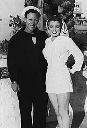 Monroe, who is wearing a white playsuit with her brunette hair tied back with a scarf, standing next to her husband Jim Dougherty, who is wearing a marine's uniform