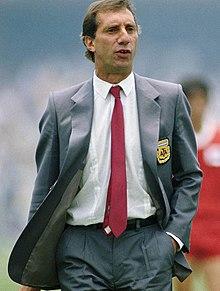 Photographie en couleurs. Un homme en costume gris, chemise blanche et cravate rouge marche vers le spectateur de la photographie, la main gauche dans la poche de son pantalon. On peut voir l'écusson de la fédération argentine de football cousue sur le costume.