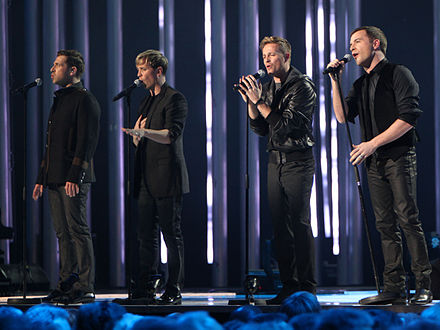 "Irish boy band Westlife achieved the first number one on the UK Singles Downloads Chart with ""Flying Without Wings"" in September 2004. Nobel Peace Price Concert 2009 Westlife2.jpg"