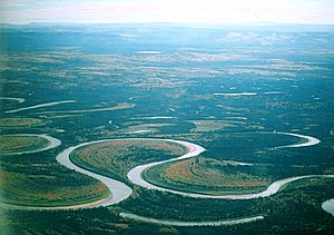 Oxbow lake - This picture of the Nowitna River, Alaska shows two oxbow lakes – a short one at the bottom of the picture and a longer, more curved one at the middle-right. Furthermore, it can be clearly seen how a third oxbow lake is in the making. The isthmus or bank in the centre of the most prominent meander is very narrow- much narrower than the width of the river. Eventually the two sections of river on either side of the isthmus will break through and create a new, straighter course. A new river bank then starts to accumulate, sealing off the meander and leaving another oxbow lake.