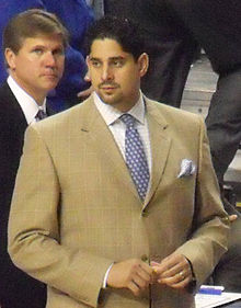 A Hispanic man in his thirties wearing a suit