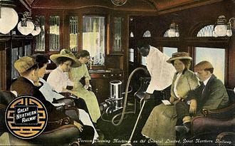 Pullman porter - A porter is shown vacuuming the carpet in a Great Northern Railway parlor car, circa 1910.