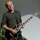 A man in a gray shirt with his eyes closed and a black guitar strapped around his neck.