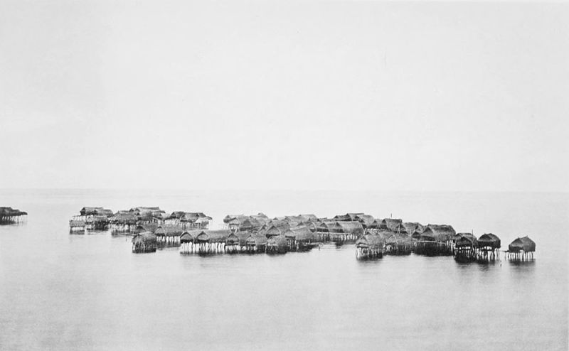 Black and white photograph of a group of about 70 native houses on stilts, entirely surrounded by water.