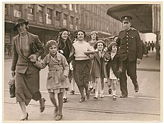 Policeman helps woman with group of girls to cross a city street, ca. 1935, from Hood Collection part II - (Children in groups and with adults, social functions, etc.), ca. 1925-ca. 1955 - Sam Hood (2965732580).jpg