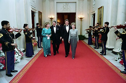 Governor and Mrs. Clinton attend the Dinner Honoring the Nation's Governors in the White House with President Ronald Reagan and first lady Nancy Reagan, 1987. President Ronald Reagan and Nancy Reagan with Bill Clinton and Hillary Clinton walking in the Cross Hall.jpg