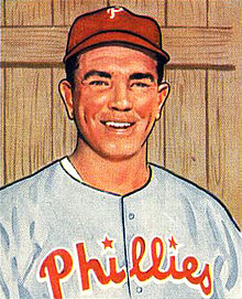 "A baseball card image of a smiling man wearing a red baseball cap and a gray baseball jersey with ""Phillies"" across the chest in red script"
