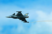 Three-quarter hind bottom view of jet aircraft in flight generating wingtip vortices, against a blue cloudy sky