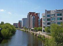 La rivière Aire canalisée coule des arches sombres sous la gare principale de Leeds vers le bas de l'image.  À gauche de la rivière se trouve l'écluse qui relie la rivière au canal de Leeds et Liverpool.  À droite se trouve une promenade au bord de la rivière sous des bâtiments modernes, et au loin, au-delà du viaduc et de la gare, se trouvent des immeubles modernes de grande hauteur situés du côté ouest du centre-ville.