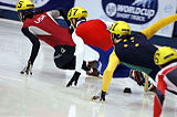 A tight group of four skaters leaning inwards as they make a turn.  The four skaters are wearing yellow helmets and suits that the display flag colors of their respective countries.  The skaters have their left hands touching the ice for balance as they accelerate around the turn.