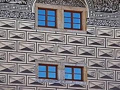 Vue des sgraffites en forme de bossages d'une façade, percée de quatre petites fenêtre à carreaux.