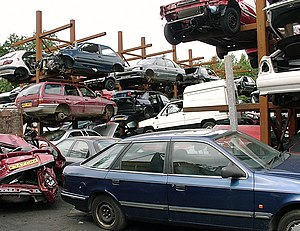 Wrecking yard - A breaker's yard in the UK, showing cars stacked on metal frames to make it easier to find and remove usable parts.