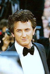 An American man with flowing dark hair, looking towards the camera, wearing a suit