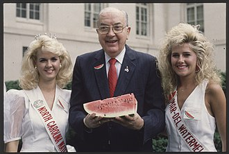 Senator Helms holding a watermelon and standing between Miss North Carolina and Miss Watermelon in 1991 Senator Jesse Helms holding a watermelon.jpg