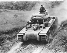 A tank cruises down an embankment in an open field while its commander stands out of the turret