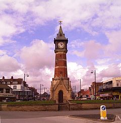 Octagonal brick and limestone tower on a square limestone base, designed like a Gothic church porch. The tower is capped with a square lantern, a white clock face on each side, heavy with Roman numerals. The towering roof is capped with a gold-coloured weathervane. The viewpoint is on the short coast road called Tower Esplanade; behind the tower is the row of tourist-trap shops in Lumley Road. The tower dominates the picture, standing out of a partly blue sky mostly filled with white, purplish, clouds. There is a ring of brick flowerbeds ringing the roundabout where the tower is. The photo was taken in May, the flower beds are just green.