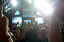 A long distance image of a stage, with video screens and floodlights falling from above. In the middle, Madonna performs