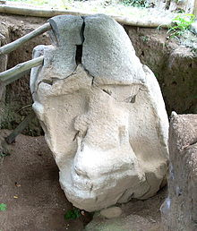 A stone sculpture sitting in an excavated trench. The monument is damaged with deep fracturing towards the top. It lists to the left and is braced with wooden poles. A niche is carved into the front of the monument and contains a badly eroded seated figure holding a featureless bundle in its arms.