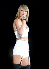 Swift performing on The 1989 World Tour. She is wearing a bob cut, a two-piece white outfit and garters while singing on a microphone