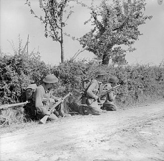 East Surrey Regiment - Men of the 1/6th Battalion, East Surrey Regiment crouch beside a hedge during fighting near Gioiella, Italy, 29 June 1944.