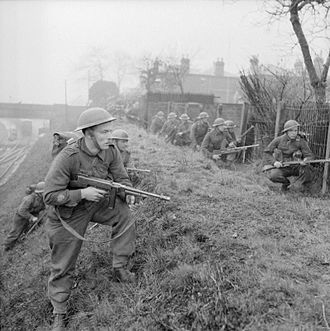 47th (London) Infantry Division - Infantry training at the 47th Division School of Battle Drill at Lymington near Southampton, Hampshire, 11 March 1942. The troops are seen advancing between the backs of houses and a railway line.