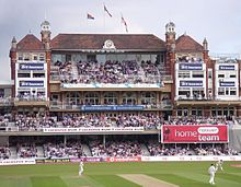 A three tiered Victorian red-brick building with flags flying on the roof and a clock at the top. There are large numbers of spectators watching a cricket match.