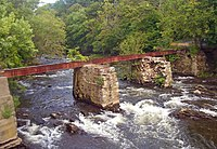 A rusted steel girder supported by two stone piers in the middle of a fast-flowing stream in a wooded area