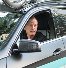 A man in his fifties behind the wheel of a car, as seen from the driver's side. He is looking out the opening left by the rolled-down window, to the left of the car.